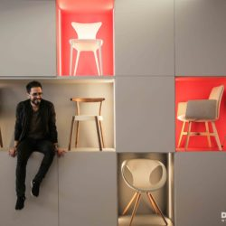 Georges Abou Chabke sitting next to designers chairs.